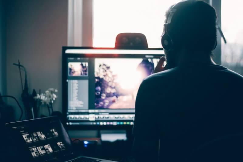 Hình ảnh được chụp từ phía sau ai đó đang ngồi vào máy tính của họ chỉnh sửa ảnh