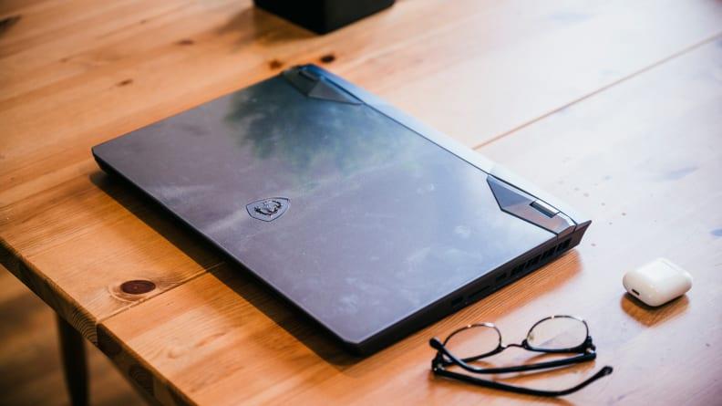 Một máy tính xách tay đóng trên đầu bàn với một cặp kính và một hộp đựng tai nghe bên cạnh.